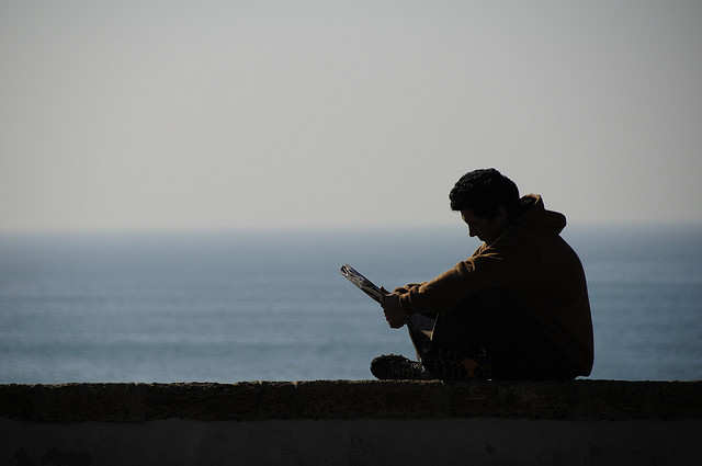 A man sits by the ocean reading the newspaper.