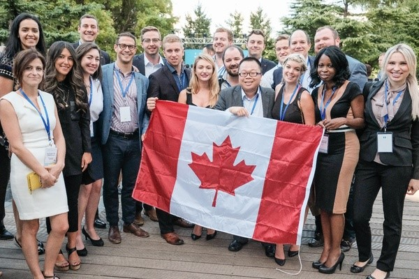 Attendees of the G20 YEA holding up a Canadian flag.