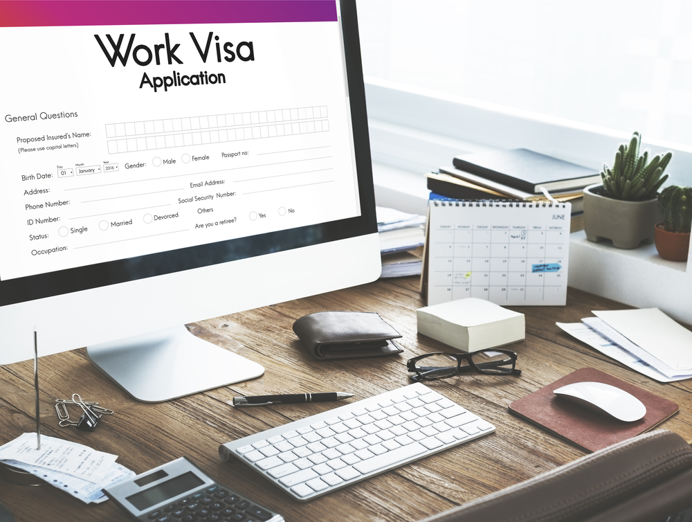 A work desk with the computer open to a Work Visa application.