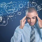 A generic stock photo of a man rubbing his temples with doodles above his head.