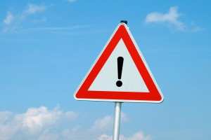 Generic stock image of an upside down yield sign with an exclamation mark on it.