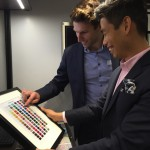 Two men happily look at colour swatches.