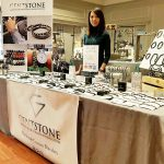 Blessy Urbi, founder of Gentstone, behind her booth of jewelry.