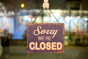 Closed sign hanging on business door.