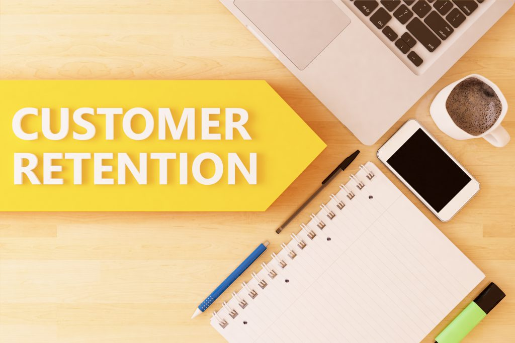 Computer and notebook on desk with customer retention arrow