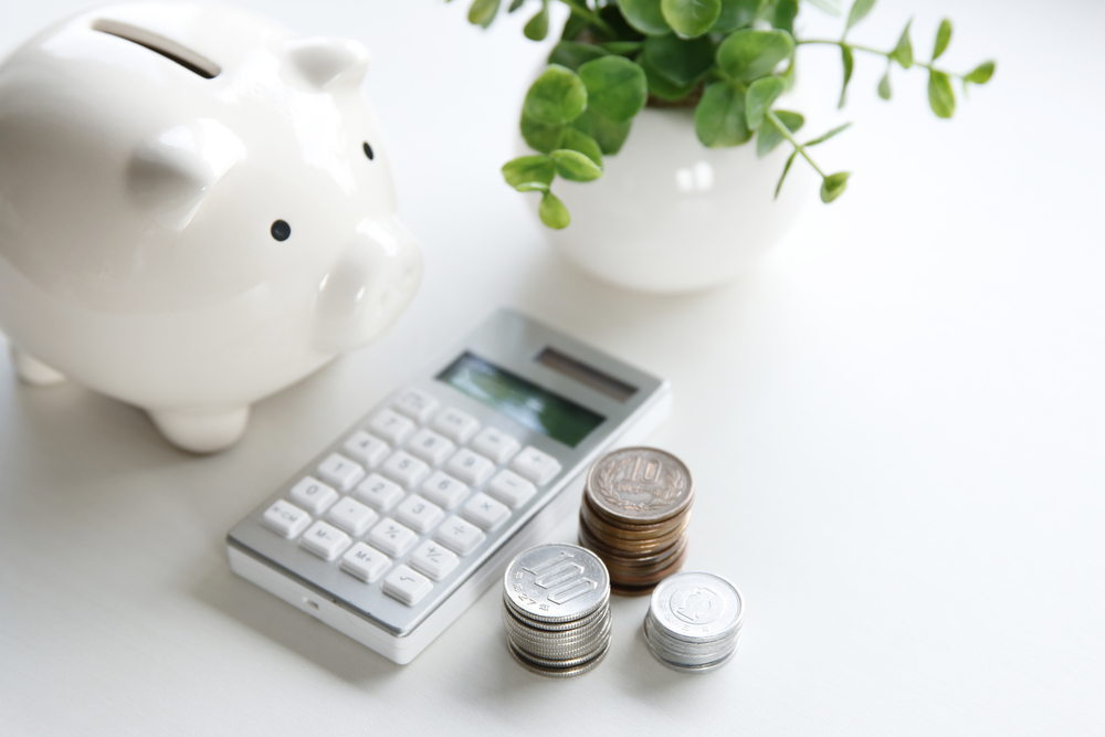 Piggy bank and calculator sitting on table with coins.