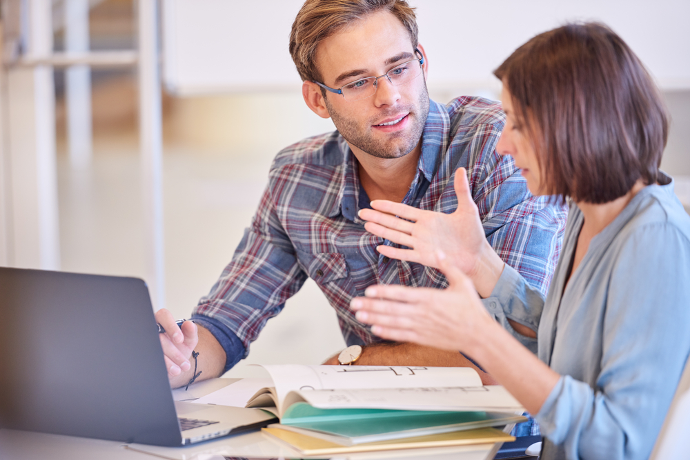Man listening to woman at computer