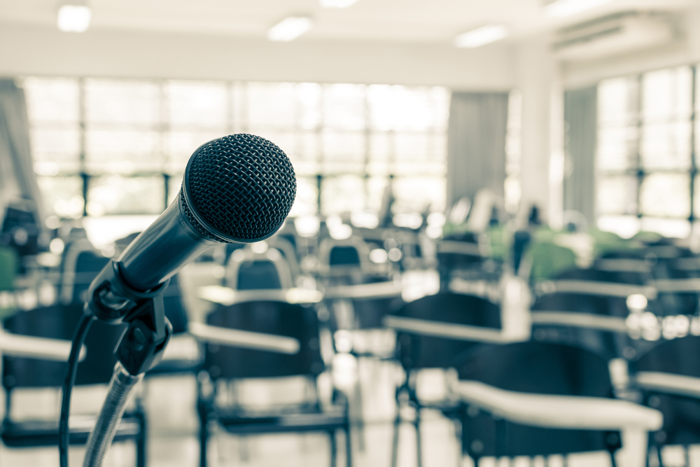 Microphone displayed at front of empty room.