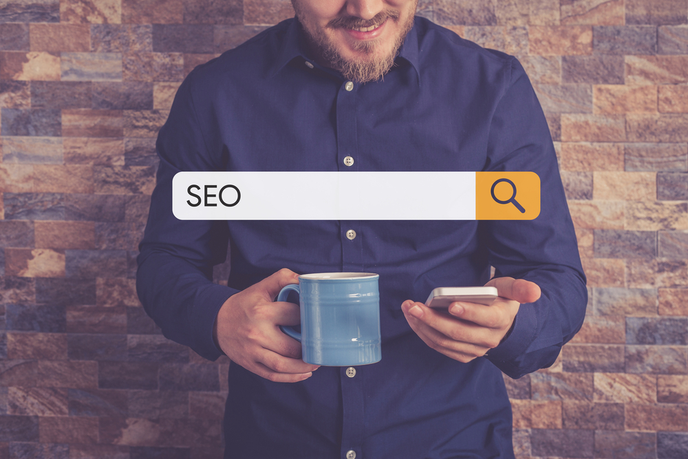 Man on phone in front of SEO search bar.