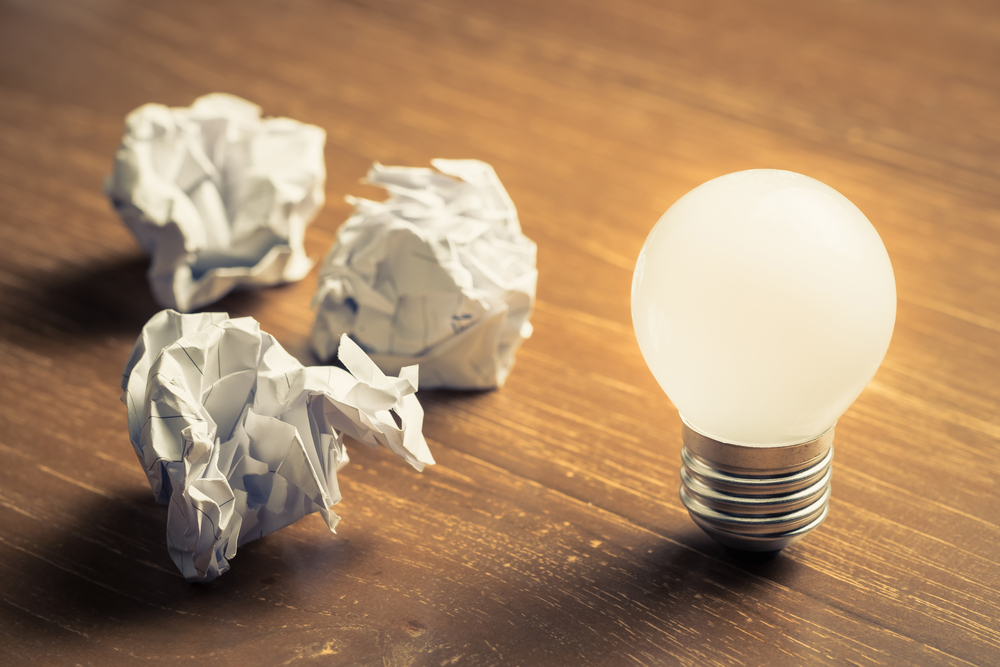 Lightbulb sitting on desk with crumpled paper behind.